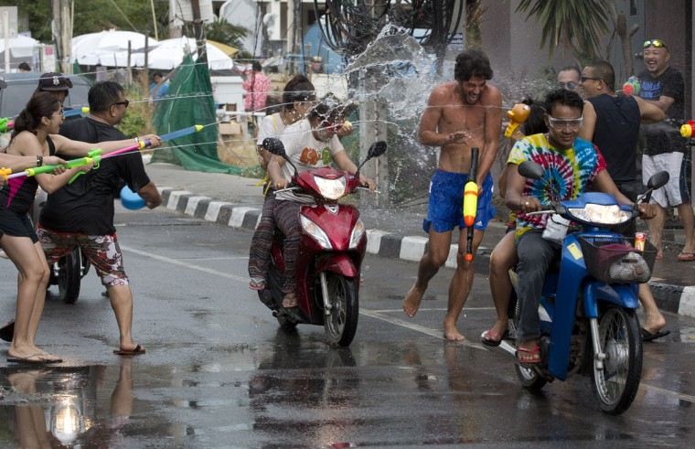 A tourist tries to escape as water is fired at him during the Songkran festival to celebrate the Thai New Year on Samui Island in Surat Thani province, Thailand, Monday, April 13, 2015. The Songkran festival, also known as the Thai New Year or Thailand Water Festival, was originally celebrated as a way for the Thai people to sprinkle water on their family members and elders for good fortune and pay their respects to images of the beloved Buddha. Today, the festival has transitioned into three days of water play fun, splashing locals and visitors alike with buckets of water, water hoses and super soakers as they gather in the streets. (AP Photo/Mark Baker)