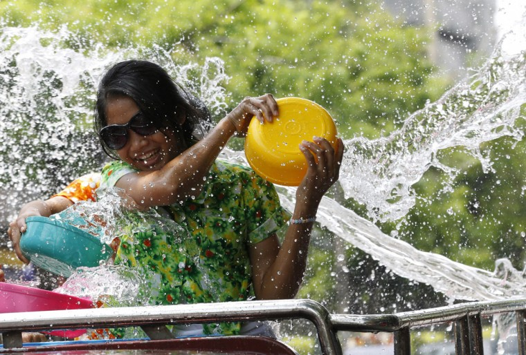A Thai woman splashes water on people on the back of a truck during the Songkran water festival to celebrate Thai New Year in Bangkok, Thailand, Monday, April 13, 2015. (AP Photo/Sakchai Lalit)