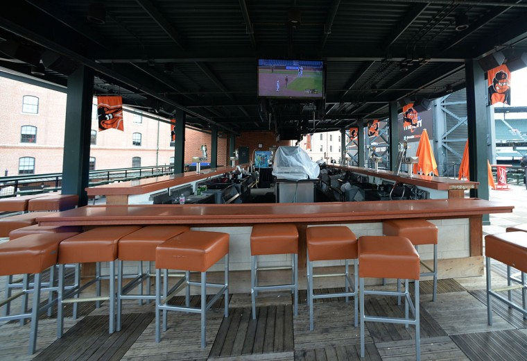 A bar showing the baseball game between the Baltimore Orioles and Chicago White Sox sits empty behind center field, Wednesday, April 29, 2015, in Baltimore. Due to security concerns the game was closed to the public. (AP Photo/Gail Burton)