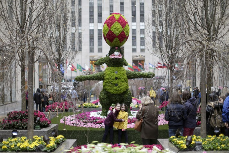 A visitors take photos with a Easter bunny topiary, Friday, April 3, 2015, at Rockefeller Center's Easter installation in New York. The installation is on display from April 2 through April 19. (AP Photo/Mary Altaffer)