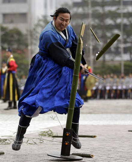 An instructor of a South Korean honor guard shows his skill of martial arts by a sword during a weekly demonstration at the War Memorial of Korea in Seoul, South Korea, Friday, April 3, 2015. (AP Photo/Lee Jin-man)