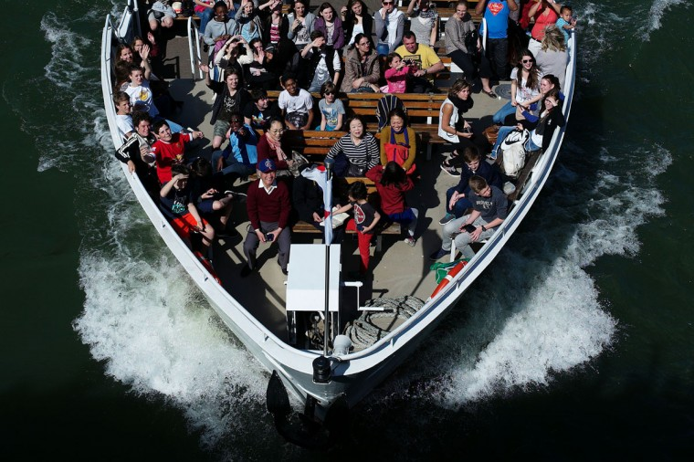 Tourists enjoy the ride while on a tour boat, in Paris, France, Tuesday, April 14, 2015. (AP Photo/Thibault Camus)