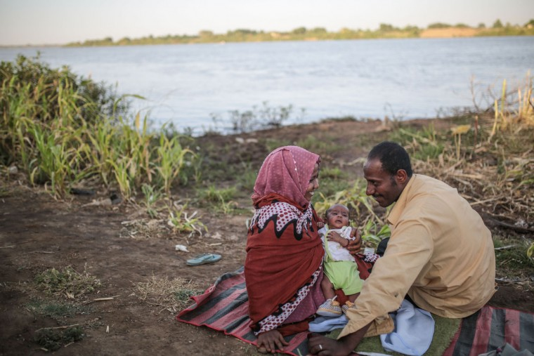 A Sudanese couple relax with their newborn son, 40-day old Mahmoud, by the Nile River bank in Khartoum, Sudan, Tuesday, April 14, 2015. (AP Photo/Mosa'ab Elshamy)