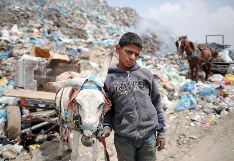 Palestinian Hussein Al-Najjar, 14-years-old, stands with a donkey-pulled cart loaded with recyclable waste and other items he collected in hope to be able to sell them, at a garbage dump in Rafah, in the southern Gaza Strip on April 16, 2015. (AFP Photo/Said said khatib)