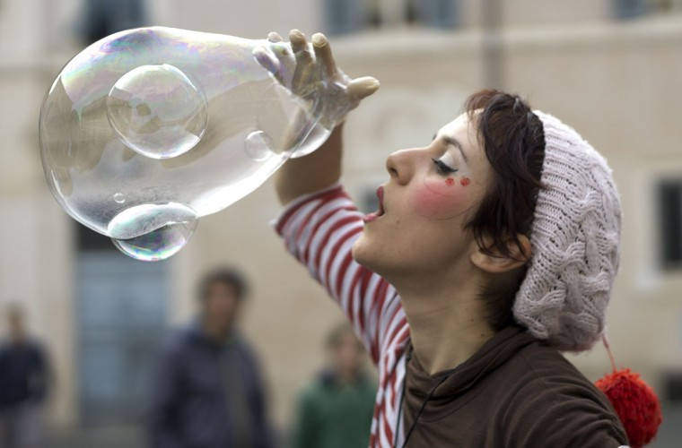 Street performer Zabo makes clustered soap bubbles in downtown Rome, Sunday, April 19, 2015. The bigger bubble is filled with two small ones. (AP Photo/Domenico Stinellis)