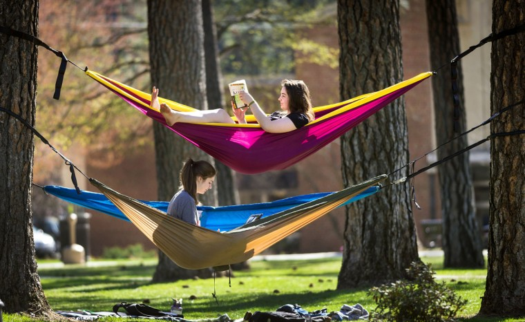 Whitworth University students Melia Deters, top, and Skyler Noble, take advantage of the warm weather to study in their hammocks strung between pine trees on campus, Monday, April 20, 2015, in Spokane, Wash. ìI like being in fellowship with people, and when you're in hammocks, it makes it even cooler,î said Deters. (Colin Mulvany/The Spokesman-Review via AP)
