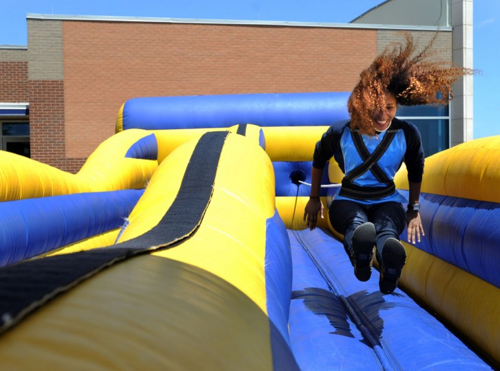 Jaileen Seballo runs on an inflatable path while strapped to a bungee cord during the Cisco College Wrangler Day, Tuesday, April 21, 2015, in Abilene, Texas. (Nellie Doneva/The Abilene Reporter-News via AP)