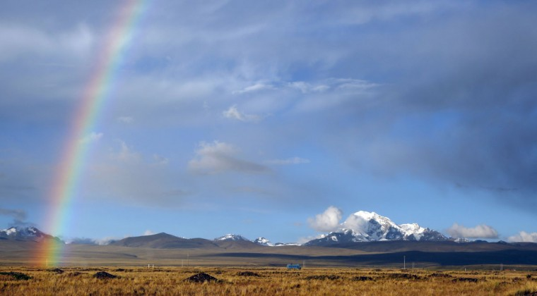 A rainbow is seen over a field with the Huayna Potosi mountain in the background as a bus drives by near Batallas, Bolivia, Saturday, April 25, 2015. (AP Photo/Juan Karita)