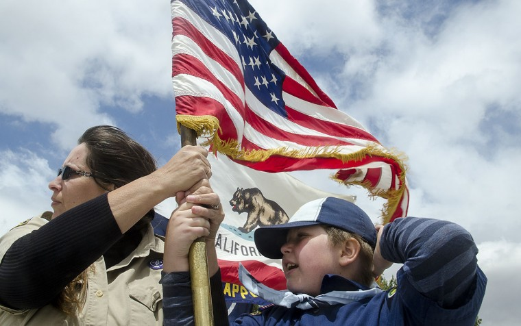 Timothy Gibb, right, of Cub Scout Pack 257 in Apple Valley, Calif, gets help holding the American flag in high winds on Saturday, April 25, 2015, for the opening of No Drugs America Day at Civic Center Park in Apple Valley, Calif. (James Quigg/The Victor Valley Daily Press via AP)