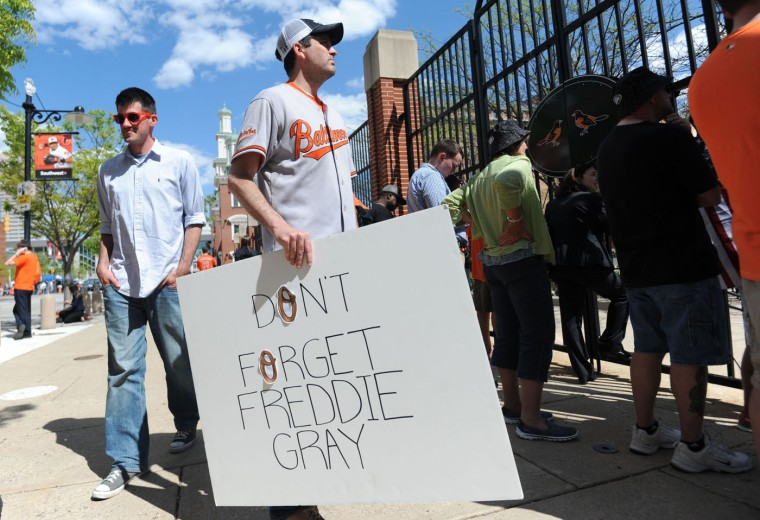 "Brendan Hurson, 37, Evergreen, a public defender who took the day off, holds a sign ""Don't Forget Freddie Gray"" as he stands with other fans outside Oriole Park at Camden Yards. (Kim Hairston/Baltimore Sun)"