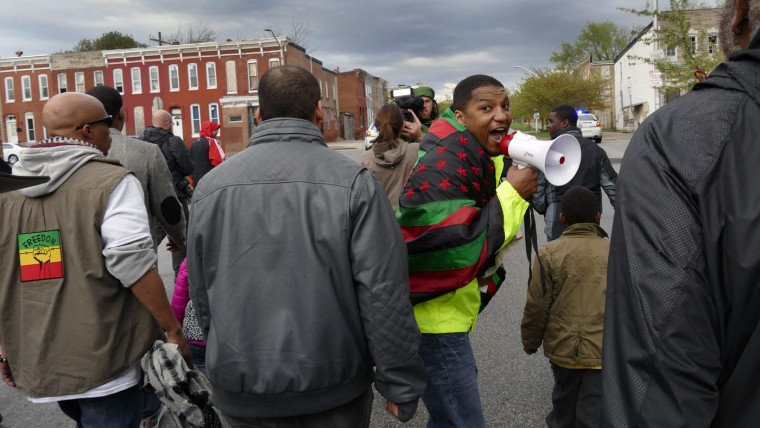 Draped in an African America flag, Abdul Salaam (who has a pending lawsuit alleging police brutality against the Baltimore city police) shouts through his bull horn as he leads protesters away from the Western District police station as marchers take to the streets for another day of protests over the death of local resident Freddie Gray, while in police custody. (Karl Merton Ferron/Baltimore Sun)