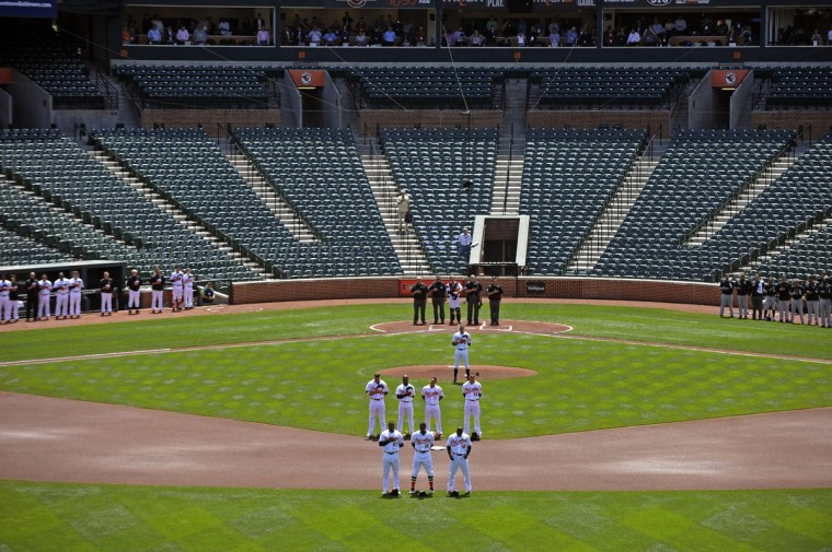 Orioles and White Sox players stand for the playing of the National Anthem. The Orioles plays the Chicago White Sox to an empty Oriole Park at Camden Yards on Wednesday. The first two games of the series were cancelled due to the wide spread riots and looting on Monday in Baltimore resulting from protest over the death of Freddie Gray. (Kenneth K. Lam/Baltimore Sun)
