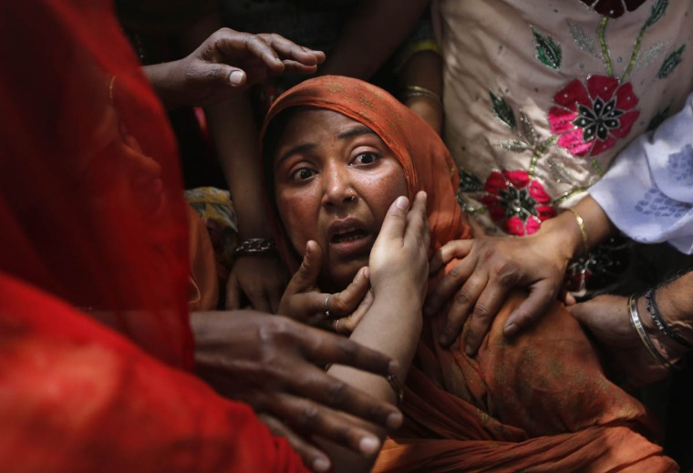 Local people console a shocked mother whose child was found under the debris of a residential building, in New Delhi, India. One man and a child were killed and at least nine others were injured when a three-story residential building collapsed following an explosion in a cooking gas cylinder, according to local news agency Press Trust of India. (Manish Swarup/AP photo)