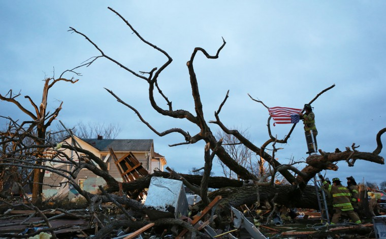 Firefighters tie a U.S. flag to a fallen tree limb at dawn Friday, April 10, 2015, after a tornado destroyed much of the town of Fairdale, Ill., the previous night. (John J. Kim/Chicago Tribune/TNS)