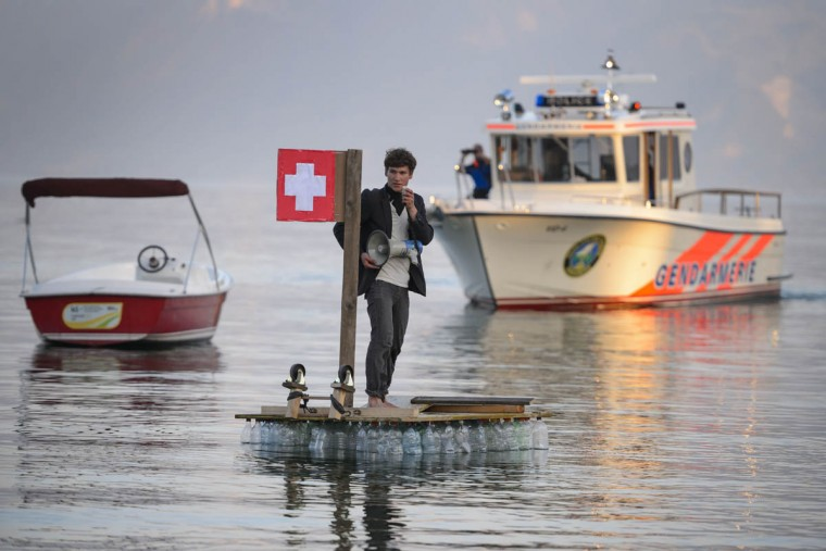 A demonstrator holding a megaphone stands on a raft bearing a Swiss flag as he protests on Lake Geneva in Lausanne, next to the hotel hosting the 2015 edition of an industry-leading Global Commodities Summit. More than 500 people took part in a protest to denounce speculation in commodities. (Fabrice Coffrini/AFP/Getty Images)