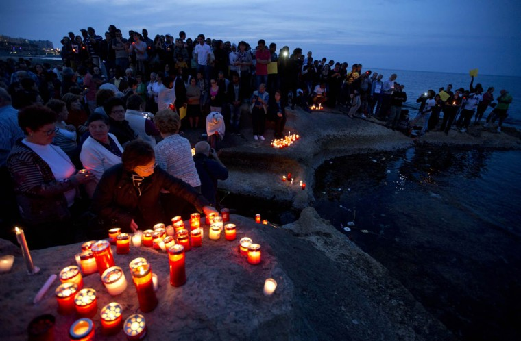 People lay candles as they pause by the sea during a candle light vigil in Sliema, in the outskirts of Valletta, Malta. A smuggler's boat crammed with hundreds of people overturned off the coast of Libya on Saturday as rescuers approached, causing what could be the Mediterranean's deadliest known migrant tragedy. The burial ceremony of the 24 rescued bodies will take place in Malta Thursday. (Alessandra Tarantino/AP photo)