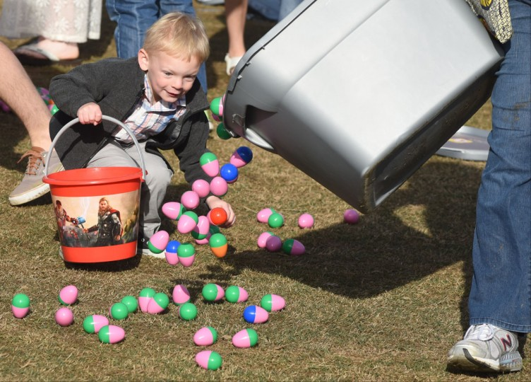 Ethan Land, age 4, follows Sharon Wennerstrom as she distributes more plastic eggs during the Easter at Coolidge event on Sunday, Apr. 5, 2015, in Chattanooga, Tenn. An estimated 100,000 plastic eggs containing candy and prizes were distributed to children before an outdoor public worship service in Coolidge Park along the banks of the Tennessee River. (AP Photo/Chattanooga Times Free Press, John Rawlston)