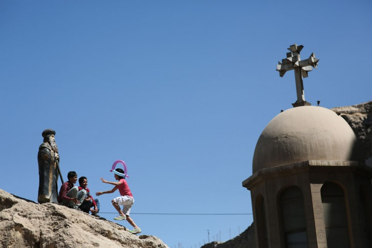 Egyptian Orthodox Christian children play on a hill as they celebrate Palm Sunday at the Samaan el-Kharaz Church in the Mokattam district of Cairo, Egypt, Sunday, April 5, 2015. For Christians worldwide, Palm Sunday marks Jesus Christ's entrance into Jerusalem, when his followers laid palm branches in his path, prior to his crucifixion. Western Christian churches and most Orthodox Christian churches follow different calendars and observe Easter on different dates. (AP Photo/Mosa'ab Elshamy)