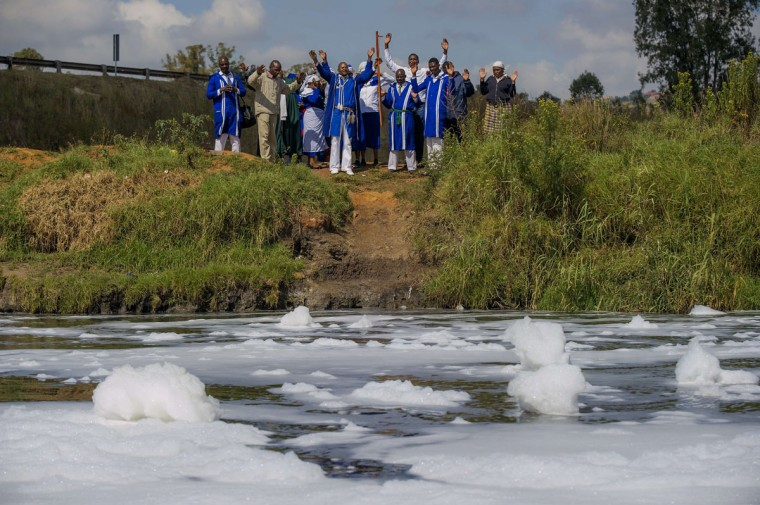 Members of the Eastern Baptist Zionist Church perform a Easter ritual at a heavily polluted bight of the Klipspruit River, in Lenasia, Johannesburg on April 5, 2015. (MUJAHID SAFODIEN/AFP/Getty Images)