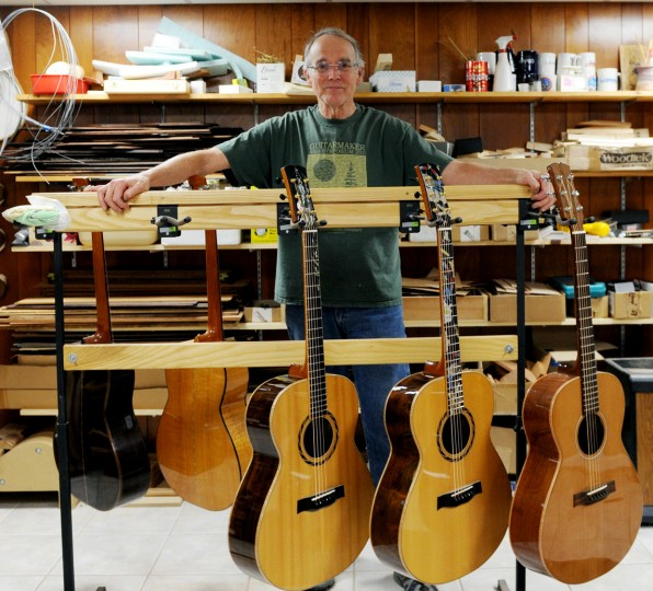 MacCubbin, of Cockeysville, poses for a photo in the basement of his home behind a rack of acoustic guitars he's made. (Jon Sham/BSMG)