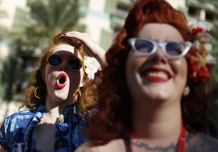 In this April 3, 2015, photo, Chelsea Spirito, left, reacts as she watches a men's bathing suit contest at the Viva Las Vegas Rockabilly Weekend in Las Vegas. Mae La Roux is on the right. (AP Photo/John Locher)
