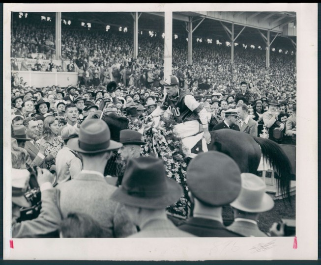TO THE VICTOR GOES THE BLANKET--Blackeyed susans, the Maryland State flower, cover the shoulders of Assault as the champion from Texas stands in the winner's circle after his 1946 Preakness triumph. Warren Mehrtens is acknowledging the cheers. (Baltimore Sun)