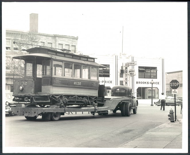 August 21, 1957: An old trolley, No. 4732, being removed from Pennsylvania Avenue Station to one near Greenmount Avenue. The photo shows the streetcar being pulled at Pennsylvania Station and North Avenue. The Brooks-Price building is pictured in the background. Photo by Sun Photographer Clarence Garrett.