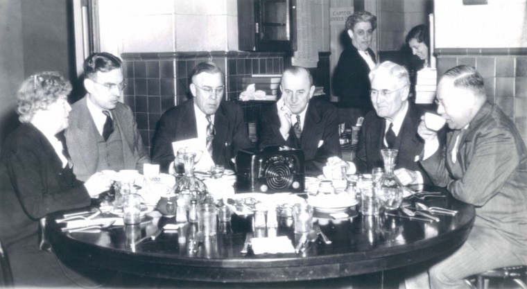 Members of Congress listen to President Truman's radio announcement of complete Allied victory over Germany as they eat breakfast in the House office building restaurant. (AP Wirephoto)