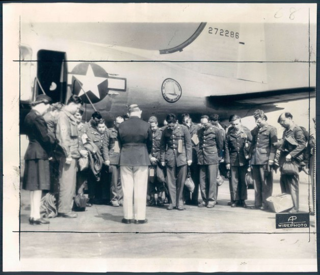 The first group of soldiers to return to the United State after news of the surrender of Germany, bow their heads in prayers offered by Capt. Edward J. Barber, Chaplain at the air transport command base at La Guardia field. All of the men were wounded in European campaigns. (AP Wirephoto from Air Transport Command)