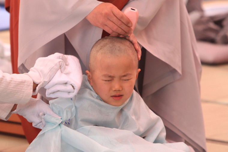 A child gets his head shaved by a Buddhist monk during the 'Children Becoming Buddhist Monks' ceremony forthcoming buddha's birthday at a Chogye temple on May 11, 2015 in Seoul, South Korea. Children have their hair shaved off during the 'Children Becoming Buddhist Monks' ceremony ahead of buddha's birthday at a Chogye temple. The children will stay at the temple to learn about Buddhism for 14 days. Buddha was born approximately 2,559 years ago, and although the exact date is unknown, Buddha's official birthday is celebrated on the full moon in May in South Korea, which is on May 25 this year. (Photo by Chung Sung-Jun/Getty Images)