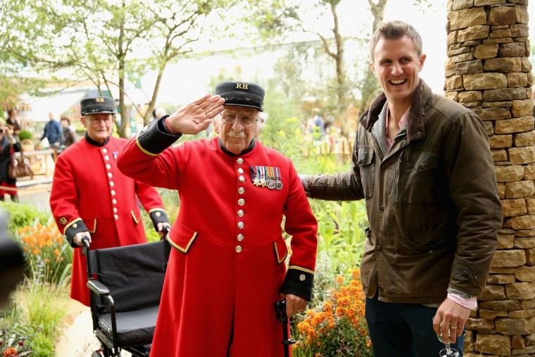 Designer Matt Keightley with a Chelsea Pensioner as he visits the Sentebale 'Hope In Vunerability' Garden during the annual Chelsea Flower show at Royal Hospital Chelsea on May 18, 2015 in London, England.The Sentebale - Hope In Vulnerability Garden at RHS Chelsea Flower Show was designed by Matt Keightley and is inspired by the Mamohato Children's Centre in Lesotho. The Children's Centre is due to open later this year in Lesotho and will provide support to children living wth HIV (Photo by Chris Jackson/Getty Images for Sentebale)
