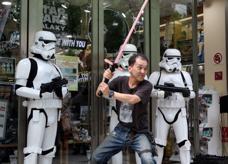 "Japanese Star Wars fan Motoi Takemura poses with Storm Troopers at a toy shop in Tokyo on May 4, 2015. May 4th is called the ""Star Wars Day"" among Star Wars fans as the famous phrase ""May the Force be with you"" in the movie sounds like ""May the 4th be with you"". (AFP Photo/Yoshikazu Tsuno)"