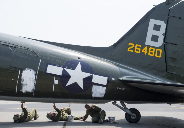 Workers with the Texas Flying Legends Museum, paint stripes on a Douglas C-53 Skytrooper airplane as dozens of World War II era aircraft gather at Culpeper Regional Airport in Brandy Station, Virginia, May 7, 2015. The planes will fly past the National Mall in Washington, DC, on May 8, during the Arsenal of Democracy World War II Victory Capitol Flyover to commemorate the 70th anniversary of Victory in Europe (VE) Day. (Saul Loeb/AFP/Getty Images)