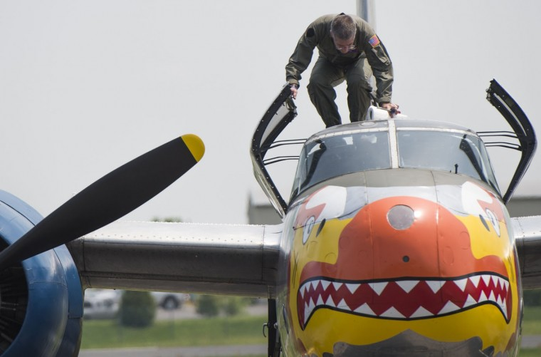 A crew member climbs in to the cockpit of a World War II era aircraft as dozens of World War II era airplanes gather Culpeper Regional Airport in Brandy Station, Virginia, May 7, 2015. The planes will fly past the National Mall in Washington, DC, on May 8, during the Arsenal of Democracy World War II Victory Capitol Flyover to commemorate the 70th anniversary of Victory in Europe (VE) Day. (Saul Loeb/AFP/Getty Images)
