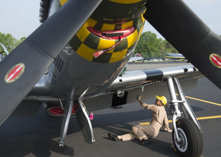A woman with the Commemorative Air Force polishes a P51 Mustang airplane prior to a practice flight with dozens of World War II era aircraft near Culpeper Regional Airport in Brandy Station, Virginia, May 7, 2015. Dozens of World War II era planes will fly past the National Mall in Washington, DC, on May 8, during the Arsenal of Democracy World War II Victory Capitol Flyover to commemorate the 70th anniversary of Victory in Europe (VE) Day. (Saul Loeb/AFP/Getty Images)