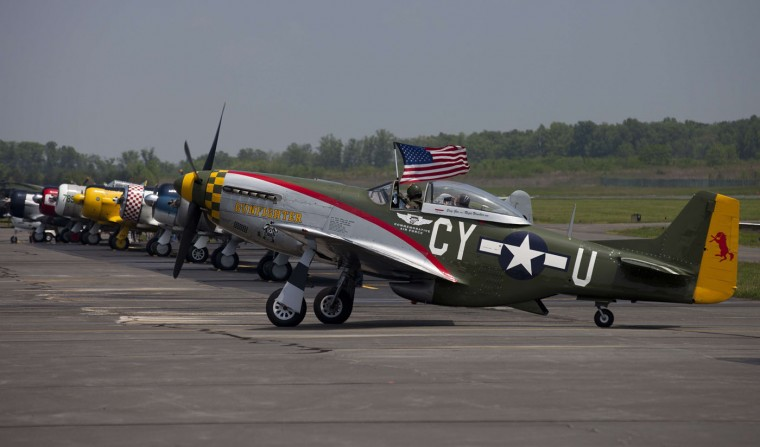 The pilot of a P51 Mustang waves the American flag after a practice flight with dozens of World War II era aircraft at Culpeper Regional Airport in Brandy Station, Virginia, May 7, 2015. Dozens of World War II era planes will fly past the National Mall in Washington, DC, on May 8, during the Arsenal of Democracy World War II Victory Capitol Flyover to commemorate the 70th anniversary of Victory in Europe (VE) Day. (Andrew Caballero-Reynolds/AFP/Getty Images)