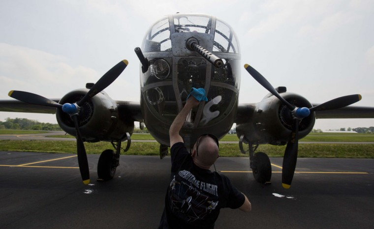 A crew member cleans the glass on a B-25 Mitchell bomber before a practice flight with dozens of other World War II era aircraft over Culpeper Regional Airport in Brandy Station, Virginia, May 7, 2015. Dozens of World War II era planes will fly past the National Mall in Washington, DC, on May 8, during the Arsenal of Democracy World War II Victory Capitol Flyover to commemorate the 70th anniversary of Victory in Europe (VE) Day. (Andrew Caballero-Reynolds/AFP/Getty Images)