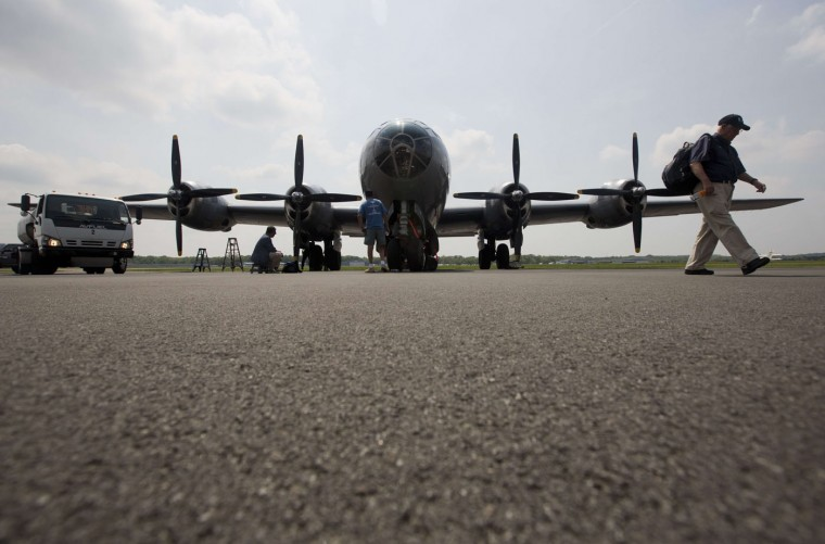 A visitor walks past a B-29 bomber after it took part in a practice flight with dozens of World War II era aircraft at Manassas Regional Airport, Virginia, May 7, 2015. Dozens of World War II era planes will fly past the National Mall in Washington, DC, on May 8, during the Arsenal of Democracy World War II Victory Capitol Flyover to commemorate the 70th anniversary of Victory in Europe (VE) Day. (Andrew Caballero-Reynolds/AFP/Getty Images)