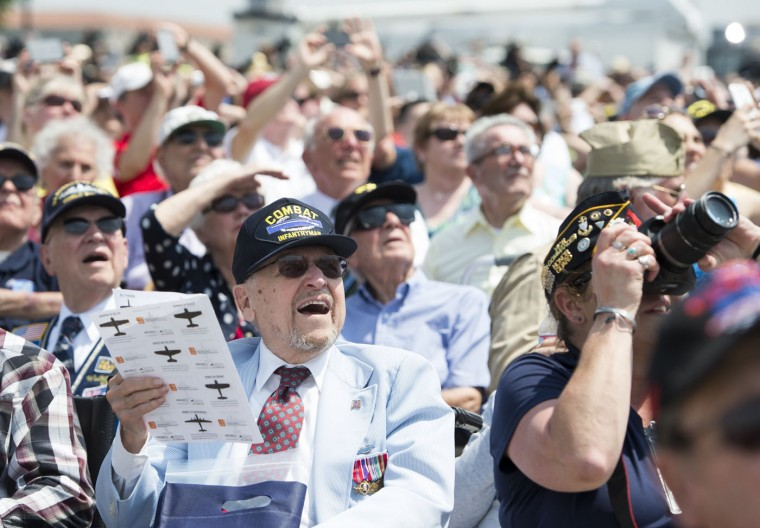 World War II veterans and their families watch as dozens of World War II era military airplanes fly over the National World War II Memorial on the National Mall in Washington, DC, May 8, 2015, during the Arsenal of Democracy World War II Victory Capitol Flyover to commemorate the 70th anniversary of Victory in Europe (VE) Day. (Saul Loeb/AFP/Getty Images)