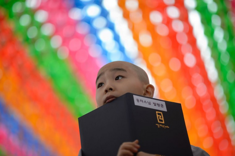 A young novice monk holds his new prayer book after having his head shaved by Buddhist monks during a ceremony entitled 'Children Becoming Buddhist Monks', at the Jogye temple in Seoul on May 11, 2015. Following the ceremony the children stay at the temple where they are taught about Buddhism, for two weeks, until Buddha's birthday on May 25. (AFP Photo/Ed Jones)