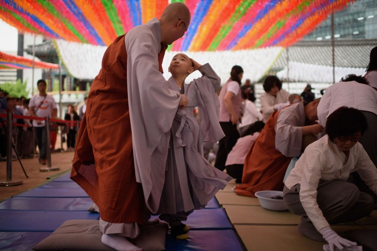 A young novice apprentice monk (C) reacts after having his head shaved by Buddhist monks during a ceremony entitled 'Children Becoming Buddhist Monks', at the Jogye temple in Seoul on May 11, 2015. Following the ceremony the children stay at the temple where they are taught about Buddhism, for two weeks, until Buddha's birthday on May 25. (AFP Photo/Ed Jones)