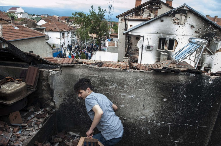 A boy walks through the rubble of a damaged house after fighting between Macedonian police and an armed group in the town of Kumanovo on May 11, 2015. Shooting broke out for a second day on May 10 in northern Macedonia as concern mounted in Europe after clashes between police and unidentified gunmen that erupted on May 9 at dawn in the restive Balkan nation left at least six officers dead along with some 30 injured. (AFP Photo/P /armend )