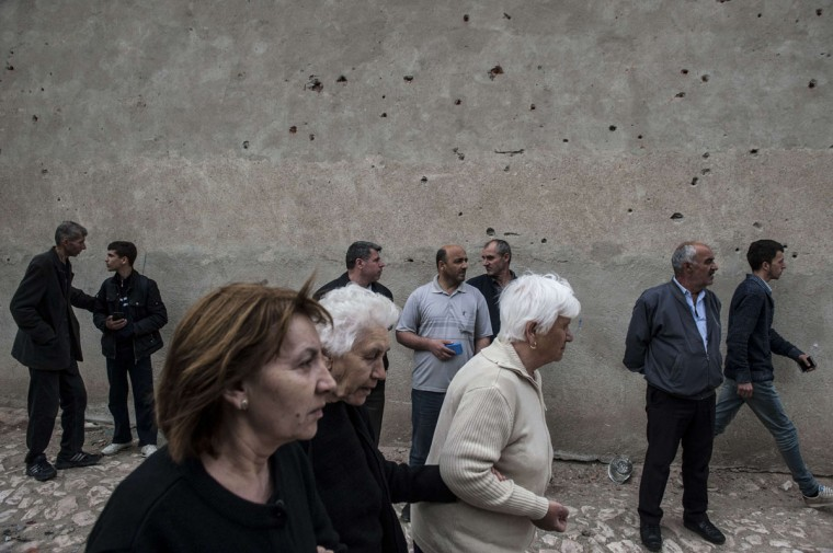 People walking in front of bullet riddled wall after fighting between Macedonian police and an armed group in the town of Kumanovo on May 11, 2015. Shooting broke out for a second day on May 10 in northern Macedonia as concern mounted in Europe after clashes between police and unidentified gunmen that erupted on May 9 at dawn in the restive Balkan nation left at least six officers dead along with some 30 injured. (AFP Photo/P /armend )