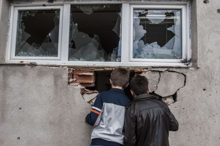 Boys look through a hole inside a destroyed house after fighting between Macedonian and an armed group in Kumanovo, some 40 kilometres (25 miles) north of Skopje, on May 11, 2015. Special police units pulled out of the northern Macedonian town early today where 22 people, including eight officers, were killed over the weekend in worst violence in the country since its 2001 inter-ethnic conflict. (AFP Photo/P /armend )