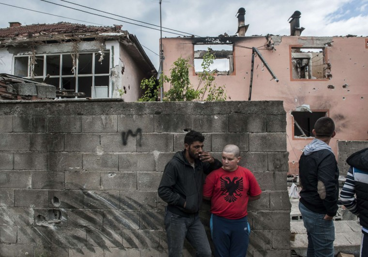 A young boy wearing a T-shirt with the colours of the Albanian flag stands next to a destroyed house after fighting between Macedonian and an armed group in Kumanovo, some 40 kilometres (25 miles) north of Skopje, on May 11, 2015. Special police units pulled out of the northern Macedonian town early today where 22 people, including eight officers, were killed over the weekend in worst violence in the country since its 2001 inter-ethnic conflict. (AFP Photo/P /armend )