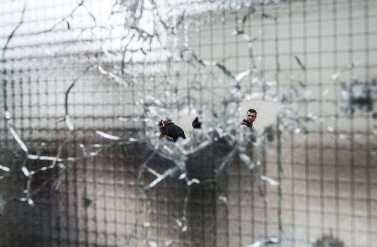 Men through bullet holes after clashes between Macedonian and an armed group in Kumanovo. Special police units pulled out of the northern Macedonian town early today where 22 people, including eight officers, were killed over the weekend in worst violence in the country since its 2001 inter-ethnic conflict. (AFP Photo/P /armend )