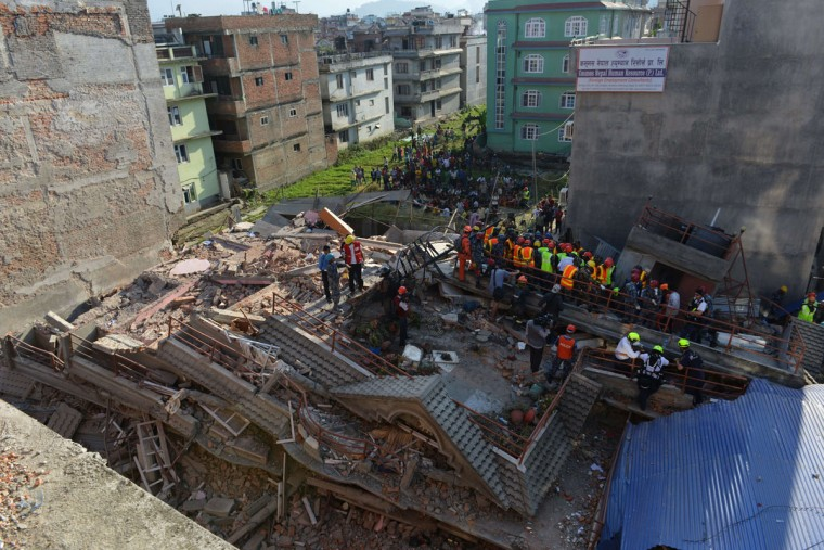 Rescue team officials search for survivors at a collapsed building in Kathmandu May 12, 2015, after an earthquake struck. A 7.4-magnitude earthquake hit has devastated Nepal, sending terrified residents running into the streets in the capital Kathmandu, according to witnesses and the US Geological Survey. The quake struck at 12:35pm local time in the Himalayan nation some 83 kilometres (52 miles) east of Kathmandu, more than two weeks after a 7.8-magnitude quake which killed more than 8,000 people. (AFP Photo/Prakash Mathema)