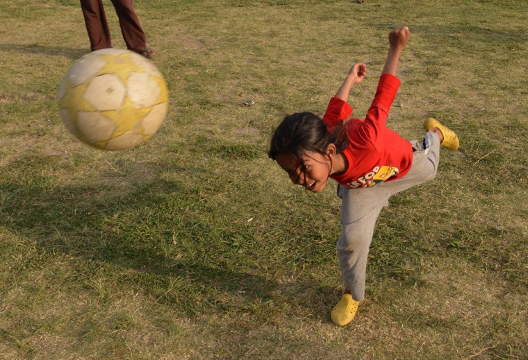 A Nepalese child plays with a football at a tent camp in Kathmandu on May 15, 2015. Nearly 8,500 people have now been confirmed dead in the disaster, which destroyed more than half a million homes and left huge numbers of people without shelter with just weeks to go until the monsoon rains. (PRAKASH MATHEMA/AFP/Getty Images)