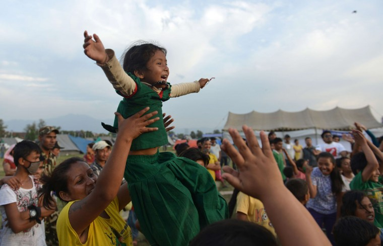 "A Nepalese mother and child participate in a ""laughter yoga"" session to help relieve trauma among survivors of two earthquakes which struck the country in less than three weeks, in Kathmandu on May 15, 2015. Nearly 8,500 people have now been confirmed dead in the disaster, which destroyed more than half a million homes and left huge numbers of people without shelter with just weeks to go until the monsoon rains. (PRAKASH MATHEMA/AFP/Getty Images)"