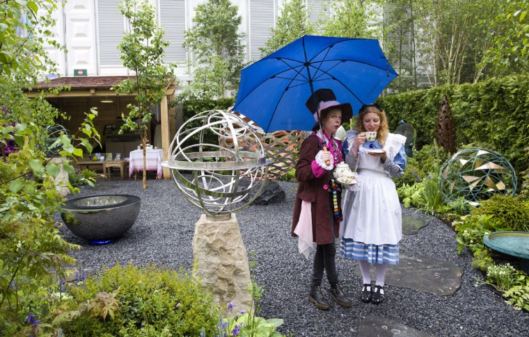 "Exhibitors dressed as ""The Hatter"" (L) and ""Alice in Wonderland"" (R) drink tea whilst sheltering from the rain under an umbrella on the David Harbor stand at the 2015 Chelsea Flower Show in London on May 18, 2015. The Chelsea flower show, held annually in the grounds of the Royal Hospital Chelsea, will run this year from May 19-23. (AFP Photo/Justin Tallis)"
